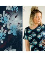 Weicher, bielastischer Jersey Stoff aus Baumwolle in einer hellen, kräftigen türkis Farbe mit hellen Kleeblumen-Muster.