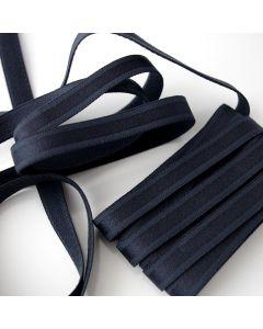BH-Trägergummiband in dunkelblau mit leicht glänzender, gemusterter Oberfläche und flauschig angerauter Rückseite.